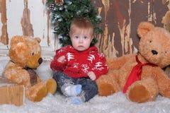 坐在两个玩具熊旁边的婴孩 免版税库存图片
