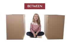 坐在两个纸板箱之间的逗人喜爱和甜金发孩子 免版税图库摄影