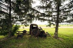 坐在两棵树之间的减速火箭的葡萄酒卡车 免版税库存照片