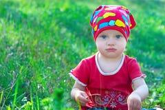 坐在中间草的红色衣裳的严肃的小女孩 图库摄影