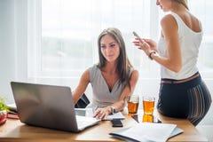 坐在书桌前面有她的coleague的便携式计算机的年轻女实业家 咖啡休息办公室 免版税库存图片