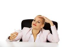 坐在书桌后和拿着玩具飞机的女商人 免版税库存照片