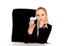 坐在书桌后和拿着玩具飞机的女商人 免版税库存图片
