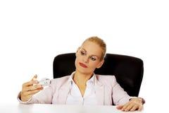坐在书桌后和拿着玩具飞机的女商人 库存照片