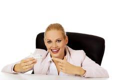 坐在书桌后和拿着玩具飞机的女商人 库存图片