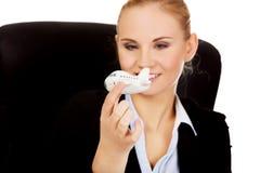 坐在书桌后和拿着玩具飞机的女商人 免版税图库摄影