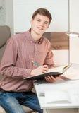 坐在书桌后和拿着课本的年轻英俊的人 免版税库存照片