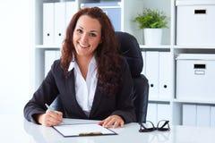 坐在书桌后的女实业家在办公室 库存照片
