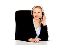 坐在书桌后的耳机的微笑的电话操作员 库存图片