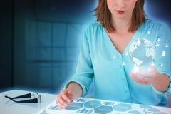 坐在书桌和使用数字式屏幕的女实业家的综合图象 免版税图库摄影