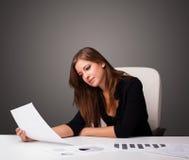 坐在书桌和做文书工作的女实业家 图库摄影
