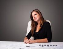 坐在书桌和做文书工作的女实业家 库存照片