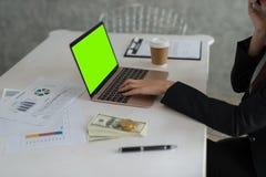 坐在书桌和工作在估计的亚裔年轻女实业家 免版税库存照片