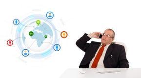 坐在书桌和打与地球a的商人一个电话 免版税库存图片