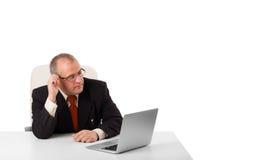 坐在书桌和看有拷贝空间的Buisnessman膝上型计算机 免版税图库摄影