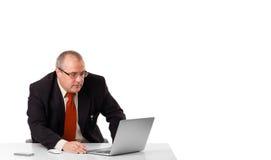坐在书桌和看有拷贝空间的Buisnessman膝上型计算机 免版税库存照片