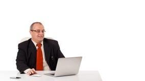 坐在书桌和看有拷贝空间的Buisnessman膝上型计算机 免版税库存图片