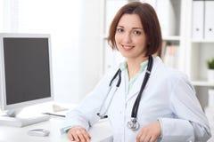 坐在书桌和研究计算机的年轻深色的女性医生在医院办公室 免版税图库摄影