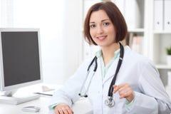坐在书桌和研究计算机的年轻深色的女性医生在医院办公室 免版税库存图片