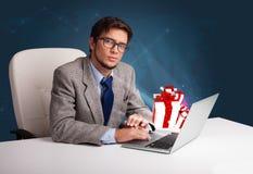 坐在书桌和键入在有当前b的膝上型计算机的英俊的人 免版税图库摄影