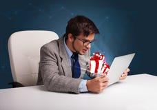 坐在书桌和键入在有当前boxe的膝上型计算机的恼怒的人 免版税图库摄影