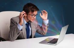 坐在书桌和键入在有抽象lig的膝上型计算机的恼怒的人 免版税库存照片