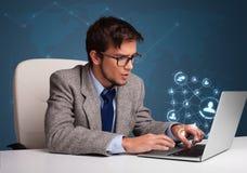坐在书桌和键入在有社会netwo的膝上型计算机的年轻人 库存图片