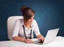 坐在书桌和键入在膝上型计算机的少妇 免版税库存照片