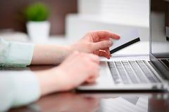 坐在书桌在办公室和研究有信用卡的便携式计算机的一件绿色女衬衫的女商人 免版税库存照片