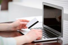 坐在书桌在办公室和研究有信用卡的便携式计算机的一件绿色女衬衫的女商人 库存图片