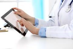 坐在书桌的医生的特写镜头 指向入片剂个人计算机的医师 医学和医疗保健概念 免版税图库摄影