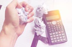 坐在书桌的商人在一个小事务所或家疯狂在工作,剥去与沮丧的手表示的文件 免版税库存照片