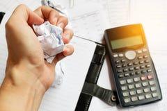 坐在书桌的商人在一个小事务所或家疯狂在工作,剥去与沮丧的手表示的文件 免版税库存图片
