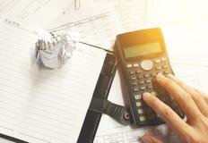 坐在书桌的商人在一个小事务所或家疯狂在工作,剥去文件 投掷在废纸附近 免版税库存图片