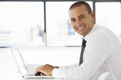 坐在书桌的商人在办公室使用膝上型计算机 图库摄影