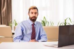 坐在书桌的商人看对膝上型计算机 免版税库存图片