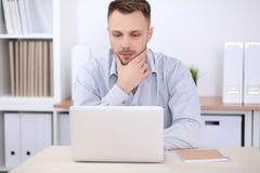 坐在书桌的商人画象在办公室工作场所 免版税库存照片