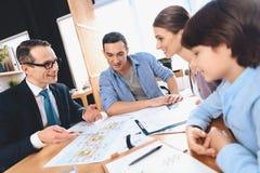 坐在书桌的地产商在办公室 地产商与父亲、母亲和儿子谈论公寓布局 免版税库存照片