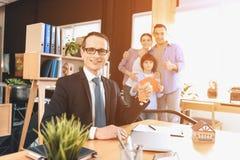 坐在书桌的地产商在办公室 地产商在背景中提出新的公寓的钥匙与家庭 库存图片