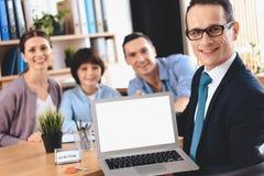 坐在书桌的地产商在办公室 地产商提出有家庭的膝上型计算机在背景中 免版税库存照片