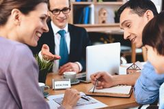 坐在书桌的地产商在办公室 父亲、母亲和儿子谈论公寓布局  免版税库存照片