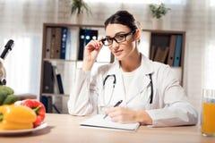 坐在书桌的女性医生在有显微镜和听诊器的办公室 妇女在剪贴板书写 免版税库存照片
