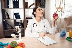 坐在书桌的女性医生在有显微镜和听诊器的办公室 妇女拿着红色苹果 库存图片