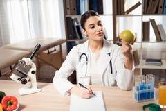 坐在书桌的女性医生在有显微镜和听诊器的办公室 妇女拿着黄色苹果 免版税图库摄影