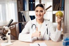 坐在书桌的女性医生在有显微镜和听诊器的办公室 妇女拿着黄色苹果 免版税库存图片