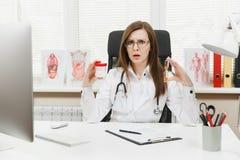 坐在书桌的女性医生,拿着有白色药片的瓶,滴漏,与在光的医疗文件一起使用 库存图片