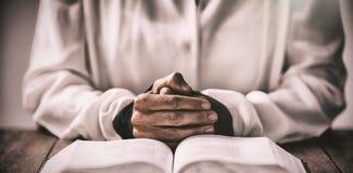 坐在书桌的妇女的中间部分由圣经 免版税库存图片