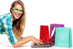 坐在书桌的少妇在网上购物 免版税图库摄影