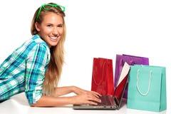 坐在书桌的少妇在网上购物 免版税库存图片