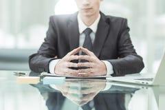 坐在书桌的年轻令人想往的商人在一台开放膝上型计算机前 库存图片